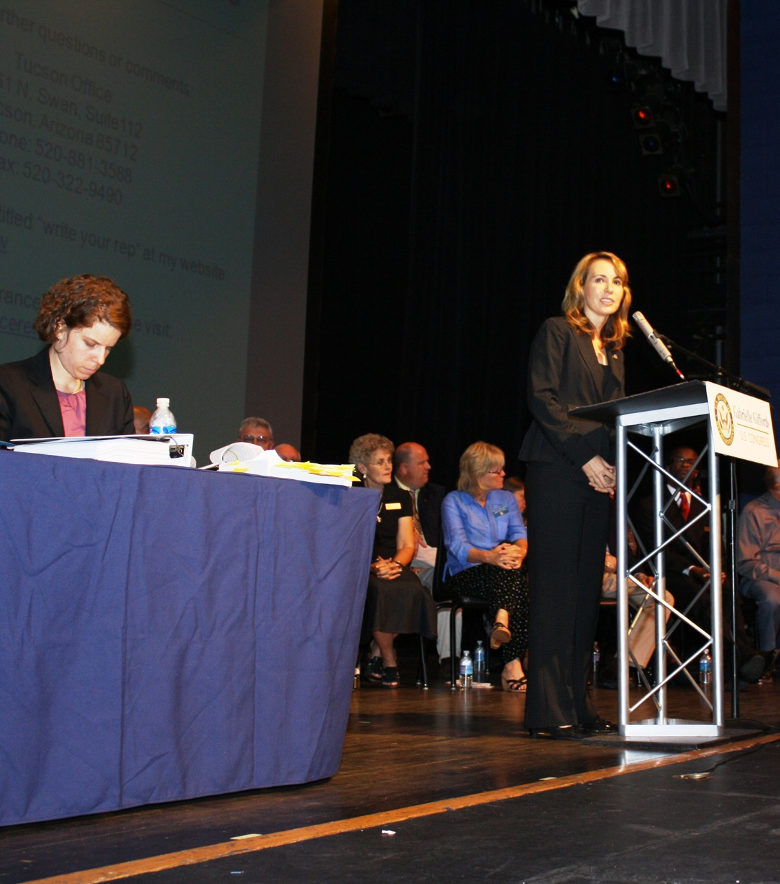 Pia Carusone behind Giffords at a Debate